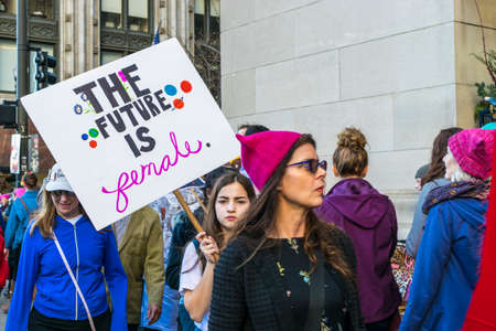 Chicago, IL, United States - January 21, 2017: Girl holds a picket sign that reads The Future Is Female during Womens March in Chicago on January 21, 2017.