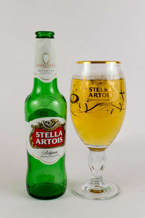 Shot of an empty bottle of Stella Artois beer next to a full glass of beer with its branding. Editorial
