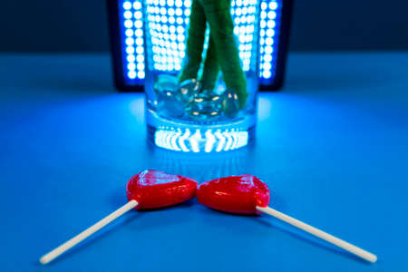 purposely: Shot of two heart-shaped lollipos next to each other on a blue background with a glass filled with stones. Lighting equipment is purposely visible in the background.