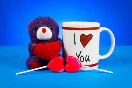 Cute teddy bear holding out a heart sitting next ot an