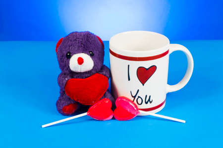 Cute teddy bear holding out a heart sitting next ot an I Love You coffee mug. Heart shaped lollipop placed right in front of the scene. Shot on blue background.