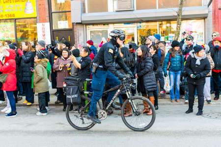 Chicago, IL, United States - February 5, 2017: Chicago police officer riding his bicycle during the Chinese New Year Parade in Chinatown, Chicago, IL.