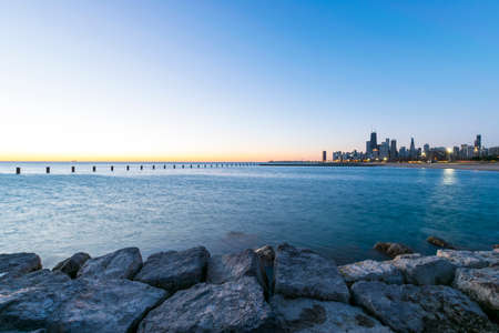 Part of Chicagos Skyline during a sunrise with a part of Lake Michigan and rocks at Fullerton Beach in the foreground.