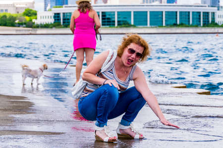 freaked: Chicago, IL, United States: June 18, 2017 - Woman is freaked by the the low temperature of water in Lake Michigan in Chicago, Illinois. Editorial
