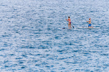 Chicago, IL, United States: June 18, 2017 - Heteresexual couple surfing in Lake Michigan in Chicago, Illinois.