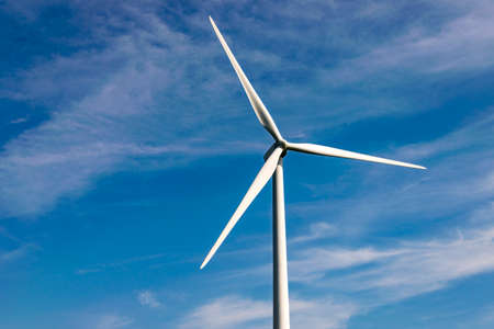 Shot of a wind turbine with a cloudy, blue sky in the background.
