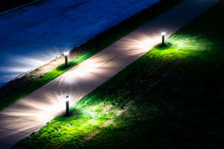 Shot of three floor lamps situated outdoors, lighting a walkway.