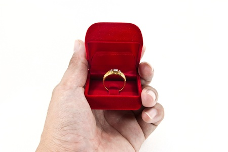 Hand holding gold ring in red box.