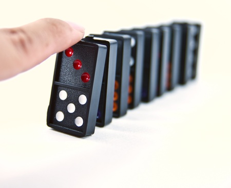 A finger ready to start domino chain reaction. photo