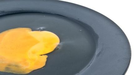 The broken yolk on black dish. Stock Photo - 10490340