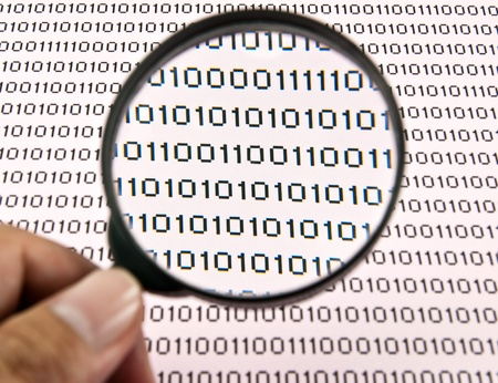 Hand holding magnifying glass. Examining binary code using magnifying glass. Stock Photo - 10767510