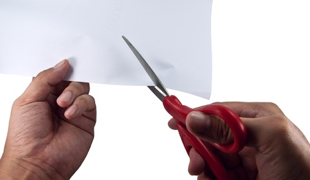 Hand is cutting paper with scissors  photo
