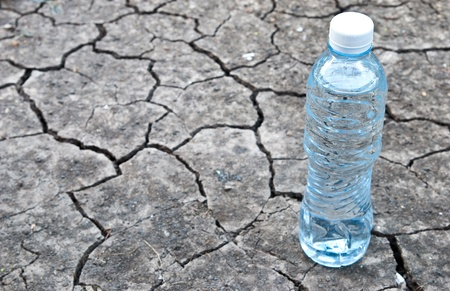 dryness: Cracked ground with water in a bottle Stock Photo