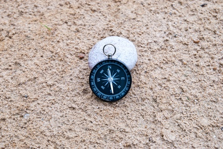 magnetic stones: Compass and stone on the sand