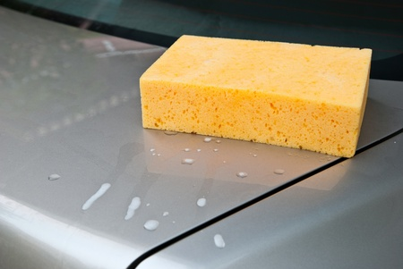 Car Wash, yellow sponge with foam on car. Stock Photo - 11474530