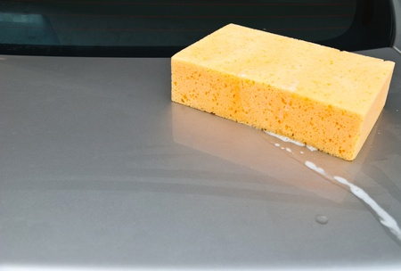 Car Wash, yellow sponge with foam on car. Stock Photo - 11474526
