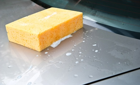Car Wash, yellow sponge with foam on car. photo