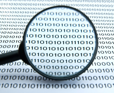 Binary code seen by magnifying glass  Stock Photo - 12672425