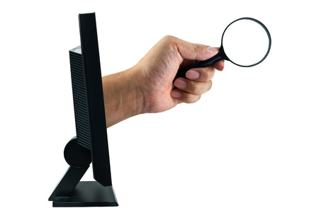 Human hand holding magnifying glass from monitor