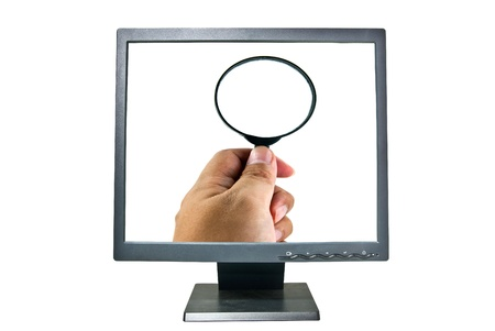 Human hand holding magnifying glass on monitor Stock Photo - 12672751