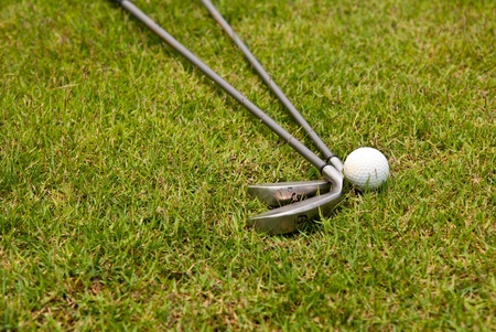 Golf ball and golf club sitting in green grass  photo
