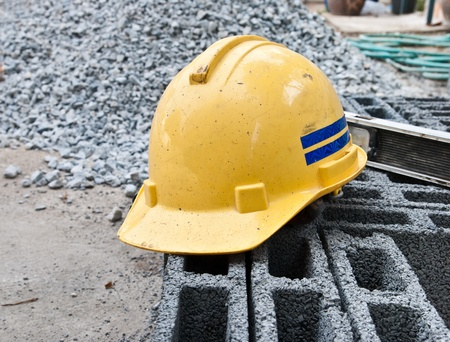 Yellow safety hard hat putting over bricks on construction site photo
