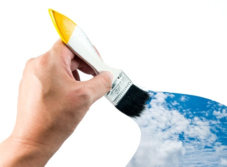 Hand holding brush and sky paint  photo