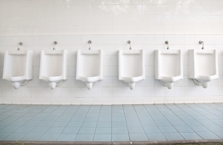 Egy sor piszoárok a csempézett falon egy nyilvános vécé