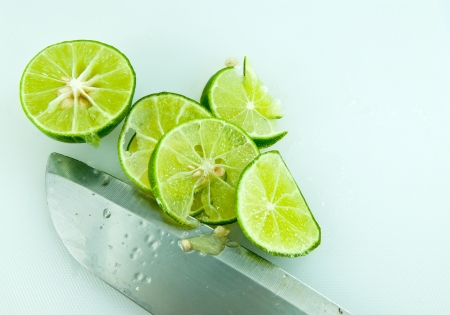 Sliced lime and knife on kitchen board  photo