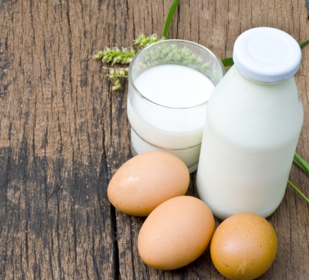 Brown eggs and milk on wooden background  photo