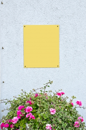 Metal plate on wall over flower bouquet photo