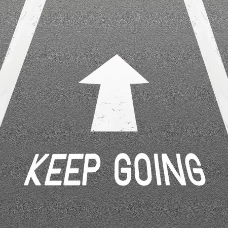 La fl�che de signalisation blanc et Word Keep Going peint sur une route fra�chement couvert avec Texture Asphalte B�ton Banque d'images