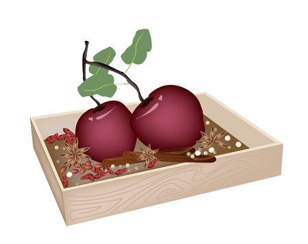 A Traditional Christmas Food of Delicious Red Christmas Apples with Cinnamon Sticks and Anise in Wooden Box for Christmas Celebration.