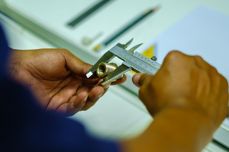 Mans hands using Vernier caliper to measure the object