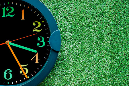 Clock on the plastic artificial green grass