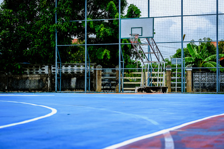 Outdoor public basketball court with blue playground rubber