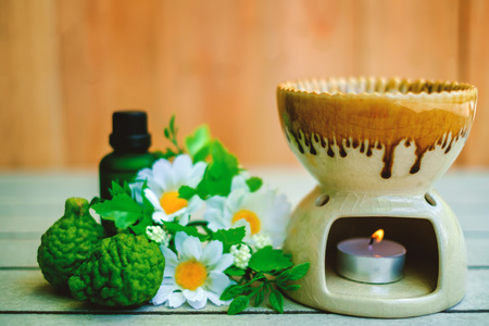 Aromatherapy essential oil burner on the wooden table with bergamot and flower for spa and relaxation