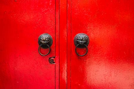 古い赤い木製のドアとライオン ヘッドのノッカー 写真素材