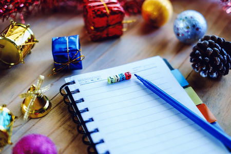 Blank notebook with letter beads wording of LIST to write down what plans to do and Christmas and New year ornaments on wooden table selective focus and added color filter Banco de Imagens