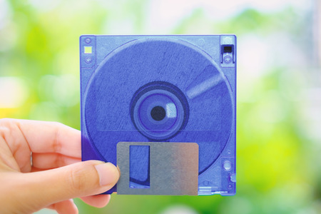 Hand holding a floppy disk against blurred background, old technology and legacy industrial computer equipment Standard-Bild
