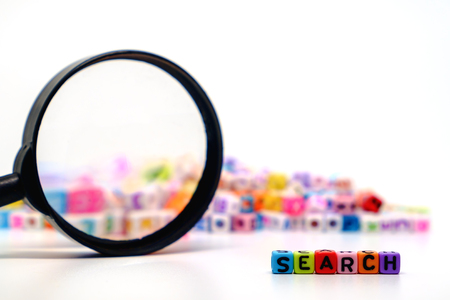 Word SEARCH on the magnifying glass with alphabet letter beads background, Search engine optimization concept Stock Photo