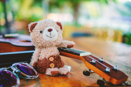 Smiling teddy bear doll on the wooden table with ukulele and sunglasses Stock Photo