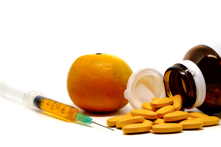 Vitamin C, pills, fresh orange, and syringe injection on white background, medical and healthcare concept 写真素材