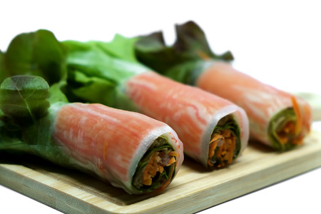 Salad roll in noodle with carrot and fresh vegetables on wooden plate and white background, heathy eating concept