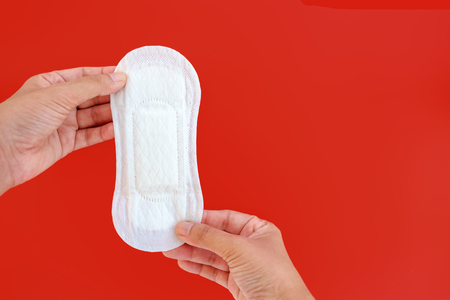Hand holding feminine sanitary napkin, an absorbent item worn by a woman while menstruating, on red background with copy space  for hygiene and health concept Stock Photo