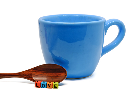 Blue cup of coffee with wooden spoon and LOVE word from alphabet letter bead on white background for cup of love and drinking concept Stock Photo