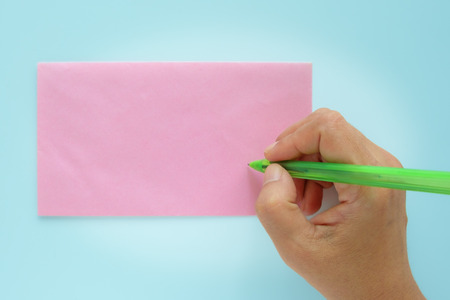 Hand being addressed on a pink envelope on blue background  Stock Photo