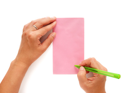 Hand holding a pen and being addressed on a pink envelope on white background