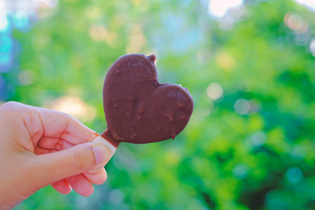 Hand holding heart chocolate ice-cream on blurred natural green background with copy space for summer sweet eating, Valentines day and love concept