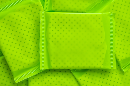 Green package of feminine sanitary napkin, an absorbent item worn by a woman while menstruating for hygiene and health concept